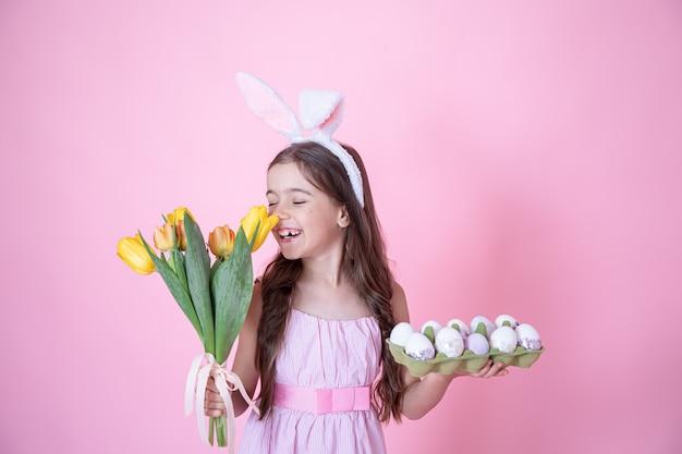 Menina com orelhas de coelho da páscoa e uma bandeja de ovos nas mãos, cheirando um buquê de tulipas em uma parede rosa.
