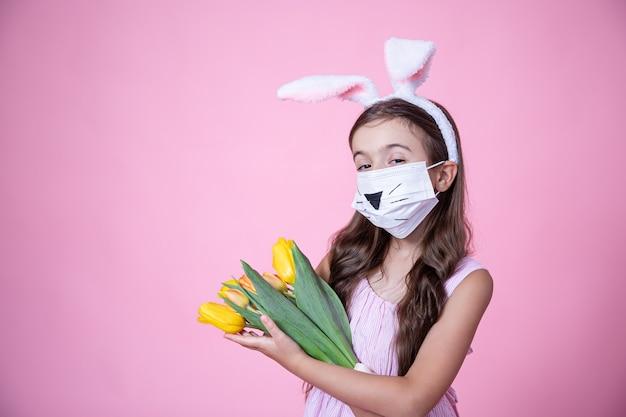 Menina com orelhas de coelho da páscoa e usando uma máscara médica segura um buquê de tulipas nas mãos em uma parede rosa.