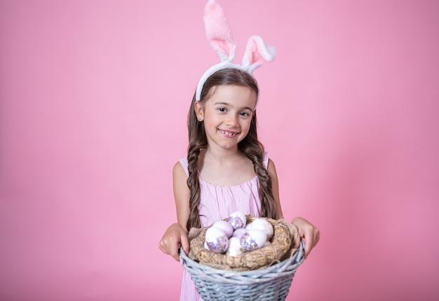 Menina com orelhas de coelho da páscoa posando segurando uma cesta com ovos de páscoa festivos em um estúdio rosa