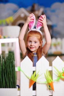 Menina com orelhas de coelho, sorrindo e fazendo careta contra a cerca branca. preparação para a celebração da páscoa.