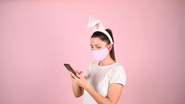 Menina com orelhas em uma máscara com um telefone. foto de alta qualidade