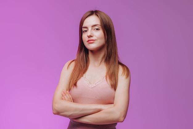 Menina com os braços cruzados contra o fundo rosa