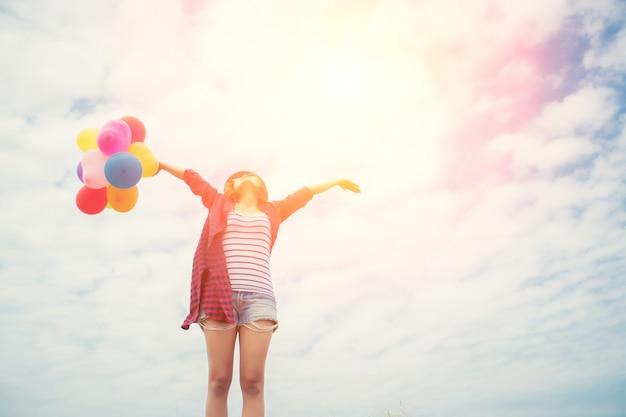Menina com os braços streched e balões coloridos