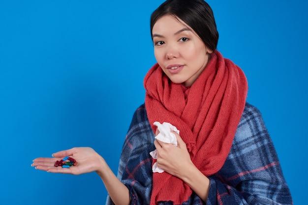 Menina com os comprimidos de tomada frios isolados no fundo azul.
