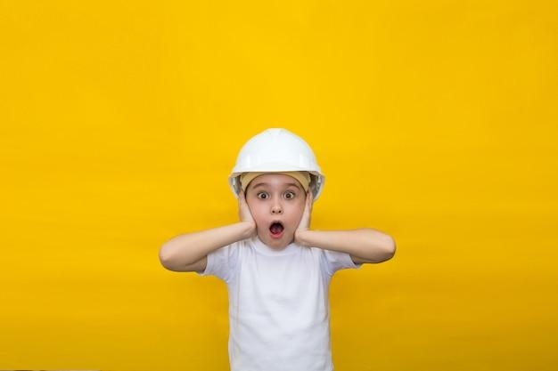 Menina com os olhos bem abertos e boca em um capacete de construção branca cobre os ouvidos