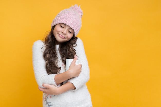 Menina com os olhos fechados, abraçando uma xícara de chocolate quente
