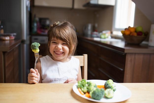 Menina com os olhos fechados comendo legumes