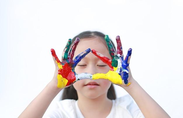 Menina com os olhos fechados e mãos coloridas pintadas