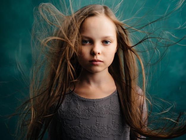Menina com os olhos fechados e o cabelo solto perto do fundo isolado