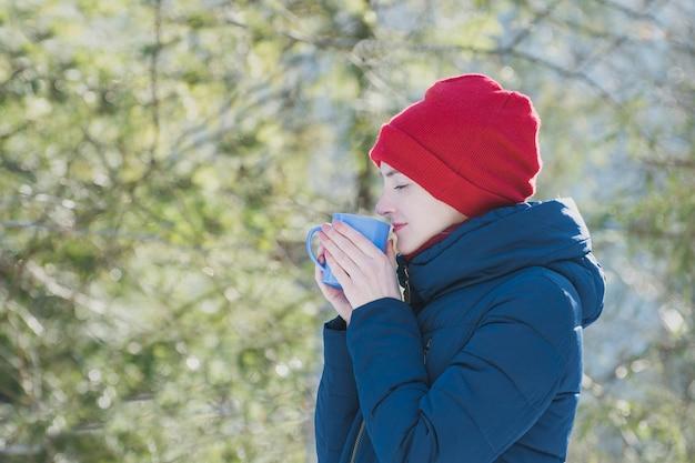 Menina com os olhos fechados em um chapéu vermelho e uma caneca na mão