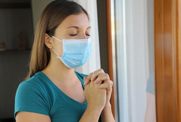 Menina com os olhos fechados orando perto da janela, usando máscara cirúrgica no rosto contra a doença do coronavírus 2019.