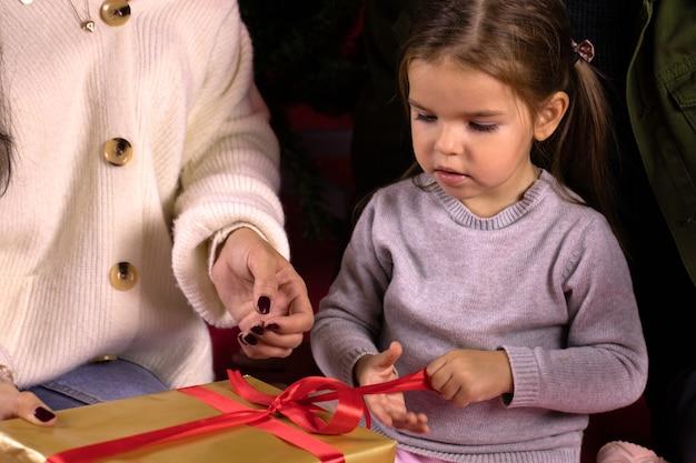 Menina com os pais abrindo um presente de natal sentada embaixo da árvore
