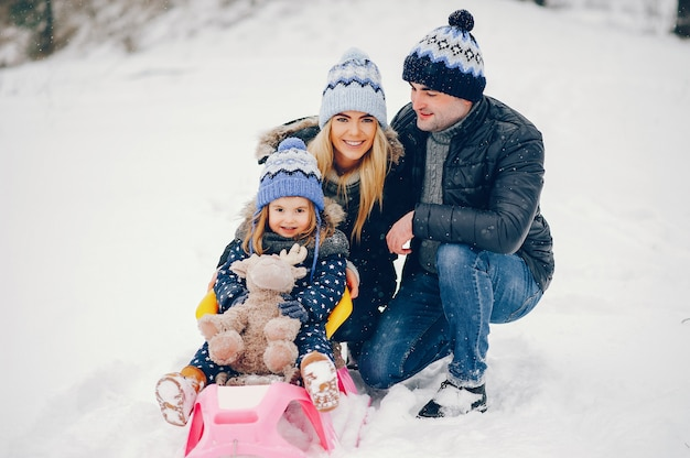 Menina com os pais brincando em um parque de inverno