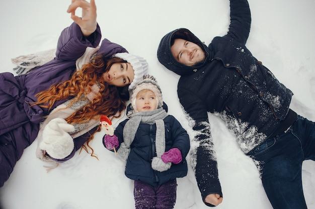 Menina com os pais em um parque de inverno