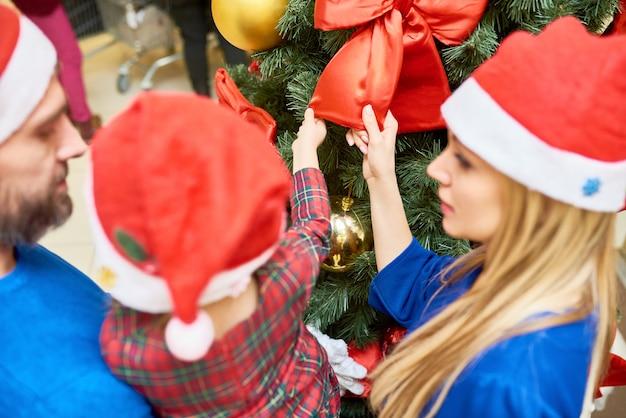 Menina com os pais na árvore de natal