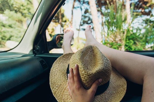 Menina com os pés fora da janela do carro tomando sol em uma tarde de verão,