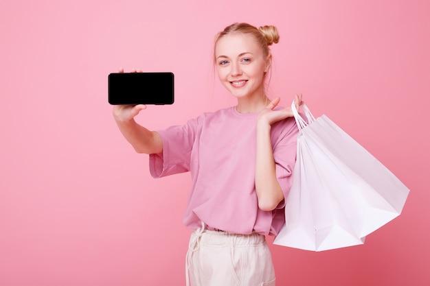 Menina com pacotes brancos de compras mostra telefone