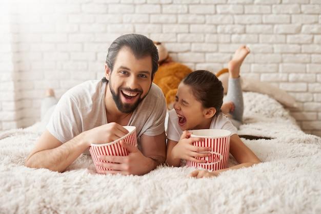 Menina com pai assistir comédia e comer pipoca