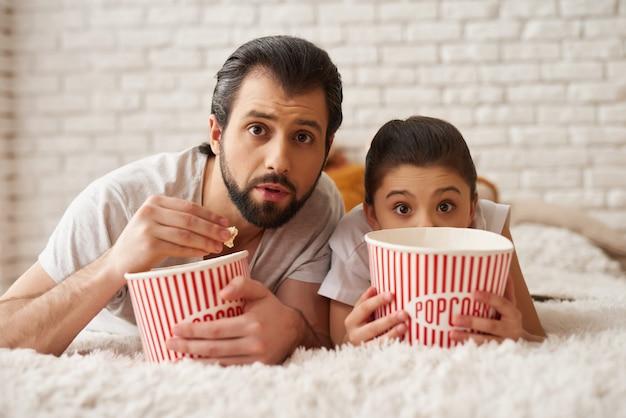 Menina com pai assistir filme assustador e comer pipoca.