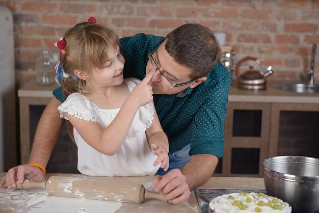 Menina com pai cozinhar na cozinha