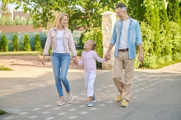 Menina com pais caminhando na rua Foto Premium
