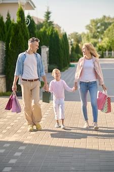 Menina com pais com malas andando pela rua