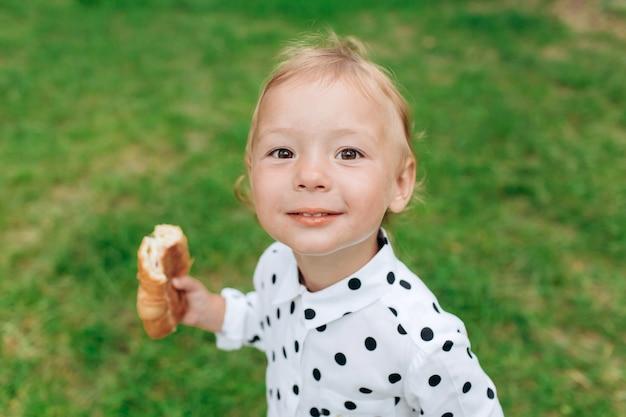 Menina com pão na mão na grama verde