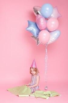 Menina com papel de embrulho e balões em uma superfície rosa