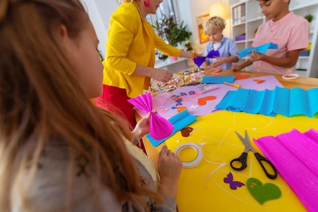 Menina com papel. menina de cabelos escuros segurando um papel rosa perto de colegas e professor