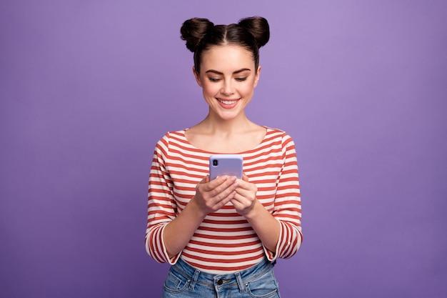 Menina com penteado da moda usando telefone isolado em roxo