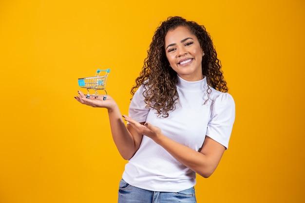 Menina com pequeno cartão de compras. sorrindo e dançando mulher de cabelo encaracolado no conceito de compras. mulher jovem com um carrinho em miniatura. comércio eletrônico e negócios. carro de compras. mulher compradora. fundo amarelo.