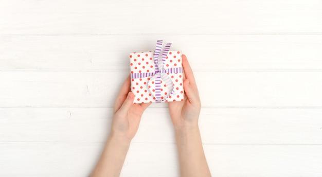 Menina com pequeno presente nas mãos dela