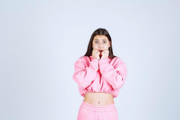 Menina com pijama rosa parece assustada e apavorada