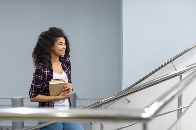 Menina com pilha de livros subir escadas