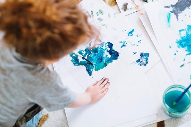 Menina com pincel de pintura em papel e sentada no chão