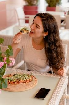 Menina com pinsa romana no café na esplanada. mulher jovem comendo pinsa e bebendo vinho.