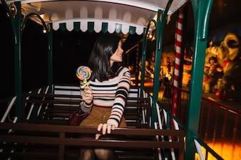 Menina com pirulito colorido em um passeio