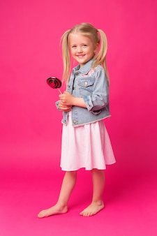 Menina com pirulito em fundo rosa