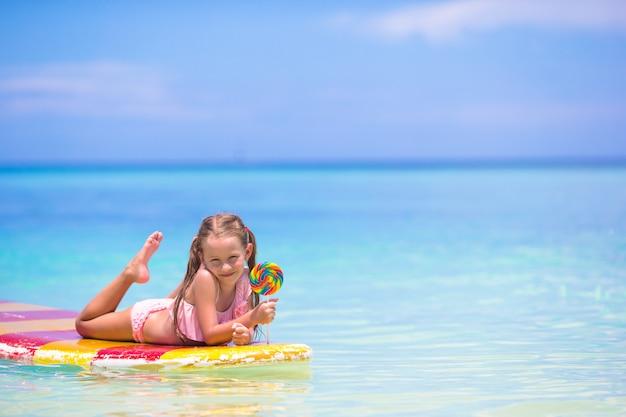Menina com pirulito se divertir na prancha de surf no mar