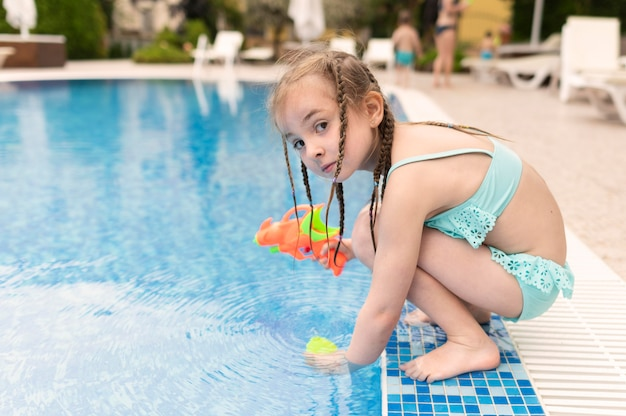 Menina com pistola de água na piscina
