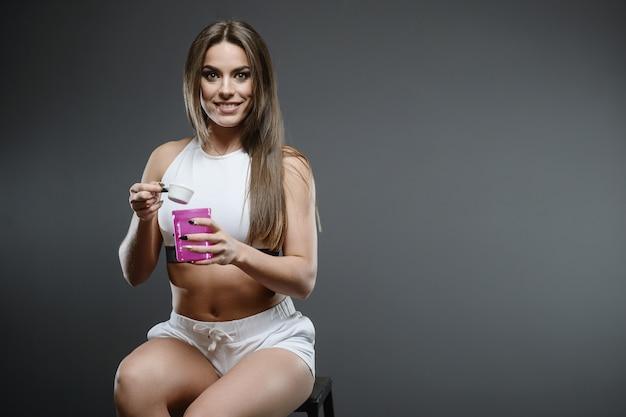 Menina com pó de shake de proteína de soro de leite suplemento