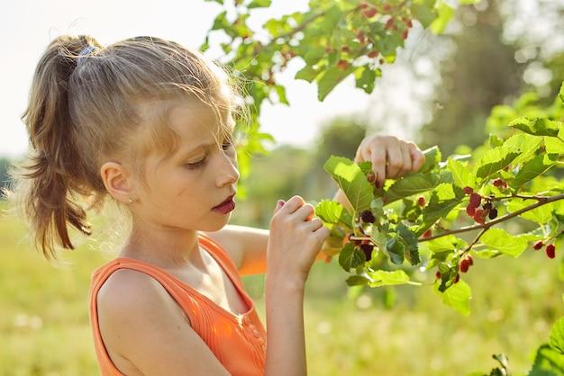 Menina com prazer comendo deliciosas frutas vermelhas maduras da amoreira