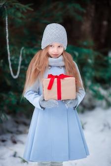 Menina com presente de caixa de natal no inverno ao ar livre