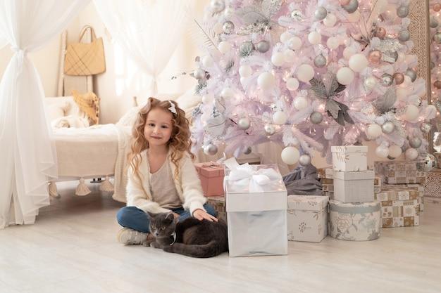 Menina com presentes e gato britânico debaixo da árvore de natal em casa.