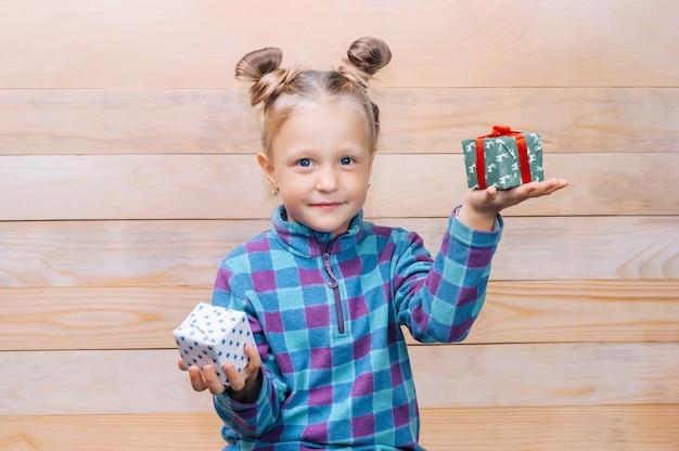 Menina com presentes nas mãos sobre o fundo das tábuas de madeira.