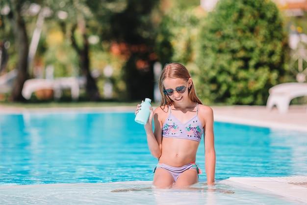 Menina com protetor solar na piscina