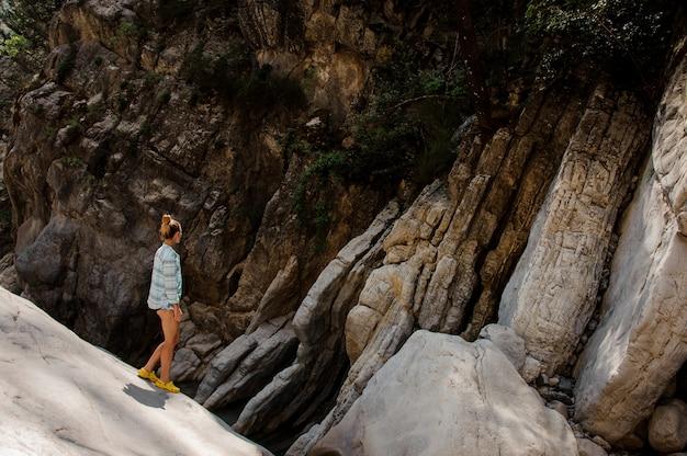 Menina com rabo de cavalo caminha sobre pedras no canyon