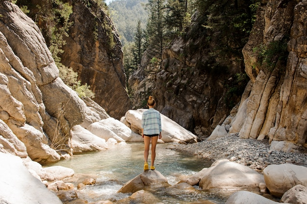 Menina com rabo de cavalo posando nas rochas no canyon