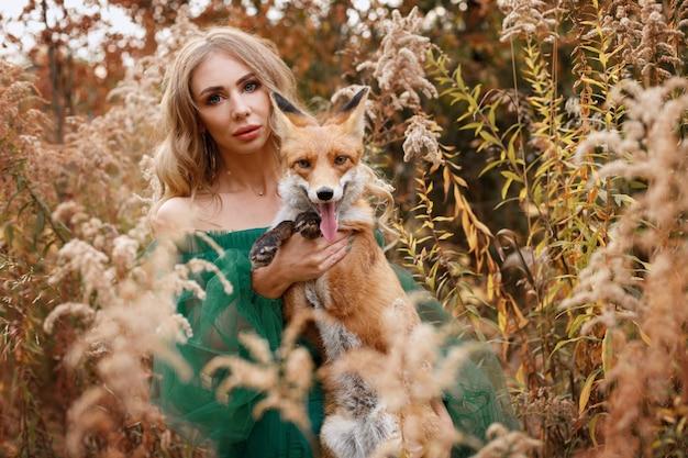 Menina com raposa vermelha no outono