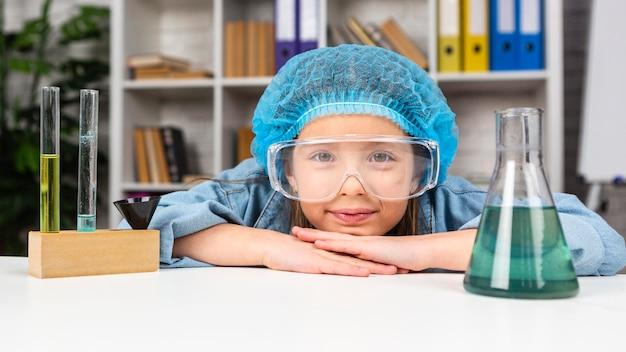 Menina com rede para o cabelo e óculos de segurança fazendo experimentos científicos com tubo de ensaio